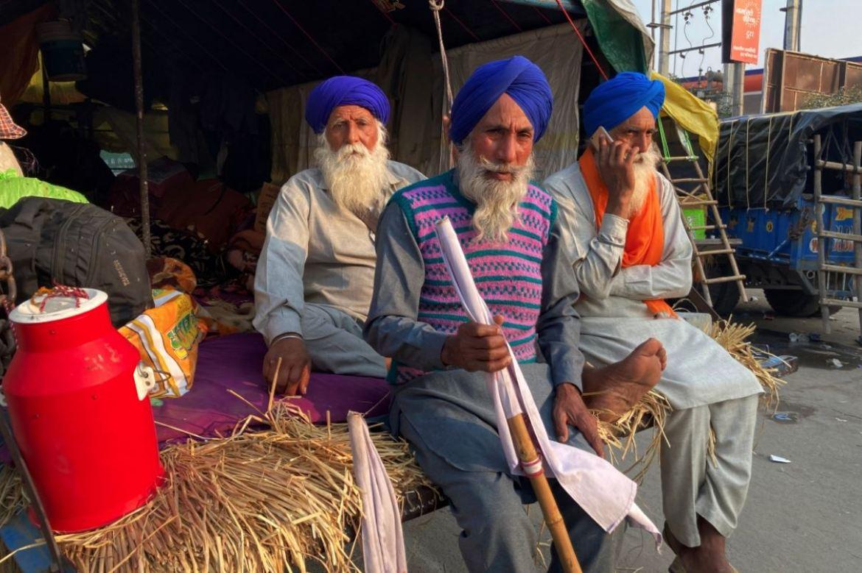 印度农民在新德里-哈里亚纳邦边界封锁交通,他们坐在拖拉机车的后方(美联社)