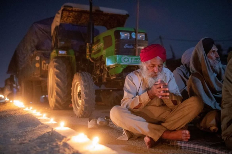在新德里附近的新湖边境抗议新通过的农业法案之际,一位农民祈祷纪念锡克教创始人古鲁那纳克诞辰551周年(路透)