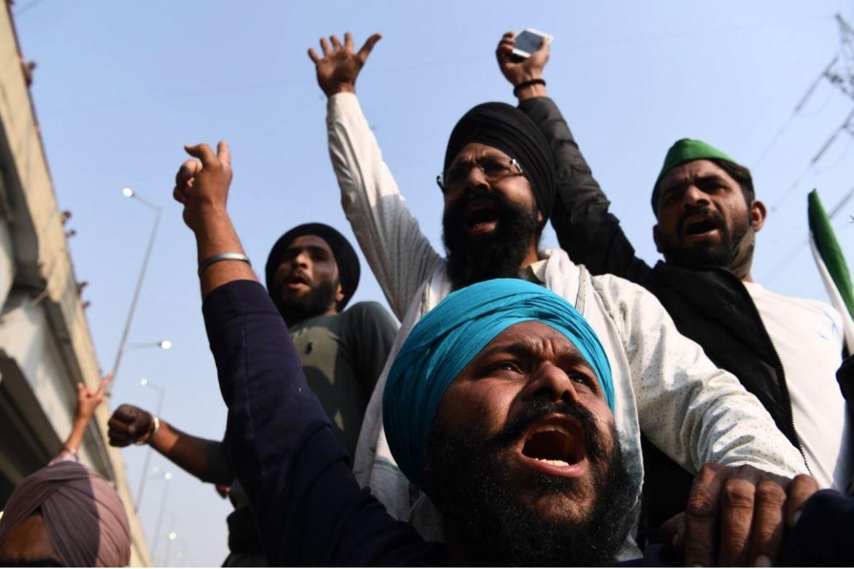 农民们在新德里-北方邦边界附近的加兹普尔图警察路障处大喊口号,该路障旨在阻止农民们前往新德里抗议政府采取的新农业政策(法新社)