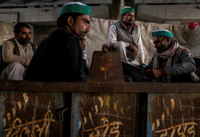 مزارعون يستريحون داخل مقطورة جرار زراعي في غازي آباد عند حدود نيودلهي وأوتار براديش (رويترز)