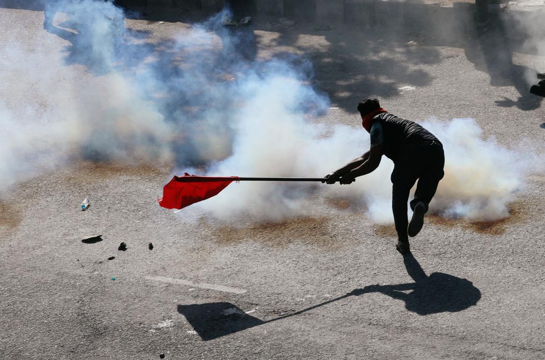 أحد المحتجين يحاول إخماد قنبلة غاز باستخدام علم (رويترز)