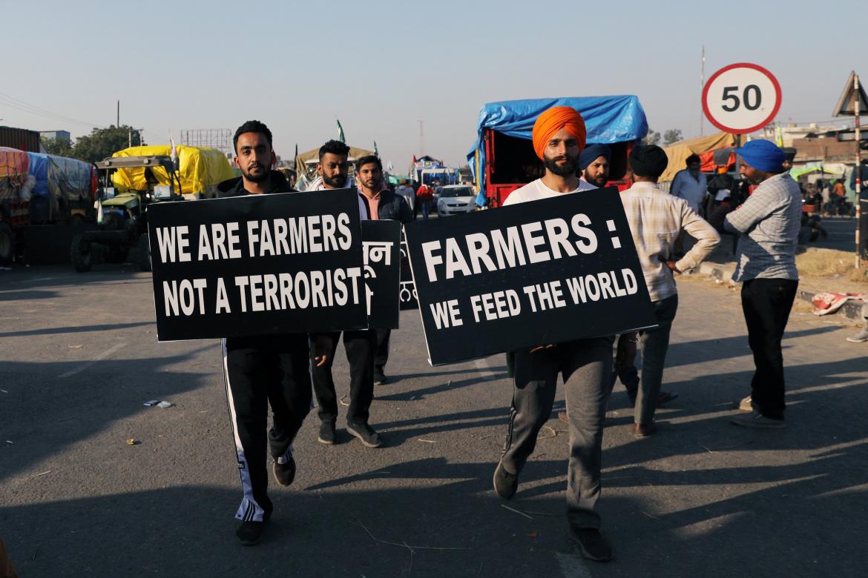 فلاحون محتجون يحملون لافتات تقول: نحن نطعم العالم.. نحن فلاحون ولسنا إرهابيين (رويترز)