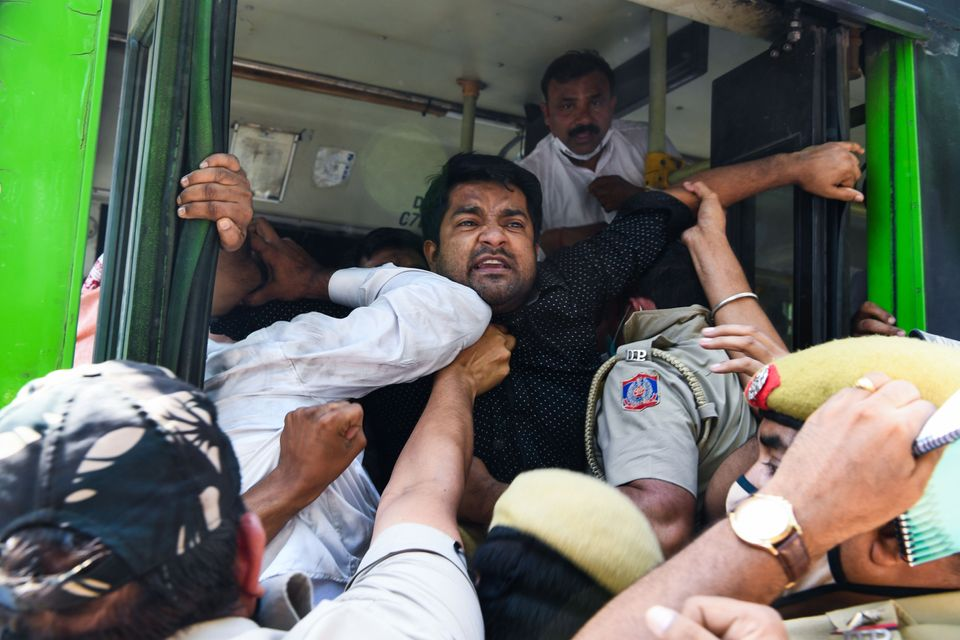 Police push Congress Party activists into a bus after detaining them during an anti-government demonstration...