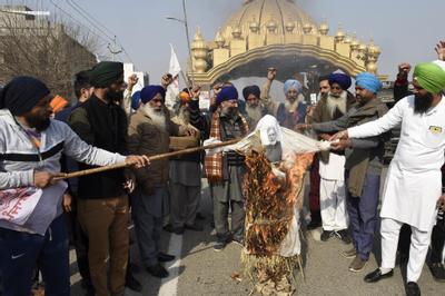 Des agriculteurs brûlent l'effigie du Premier ministre indien Narendra Modi dans la périphérie d'Amritsar, ce 2 février 2021.