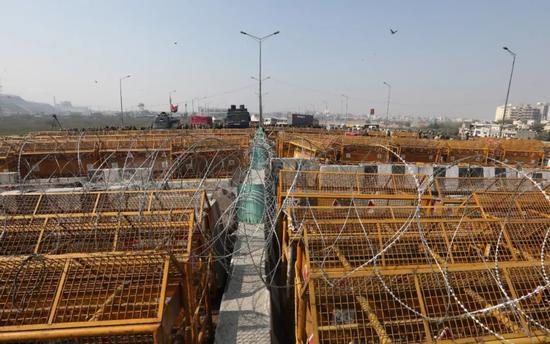 当地时间2月6日,印度新德里,数千名农民聚集在城郊,试图穿越由铁丝网和路障构成的封锁线,抗议政府推出的农业改革法案。警察驻扎在封锁线另一端,与农民形成对峙之势。图/IC photo