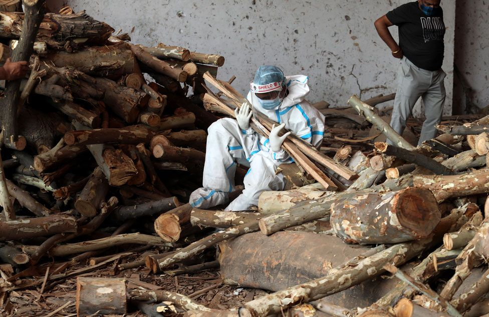 A person sits on the ground clutching wood at a cremation ground in New Delhi, India