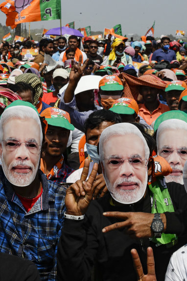 Supporters rally wearing masks of Prime Minister Narendra Modi during election campaigning in West Bengal.