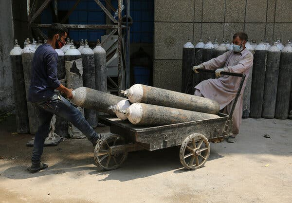 Workers carrying oxygen cylinders at a government run hospital in Jammu on Friday.