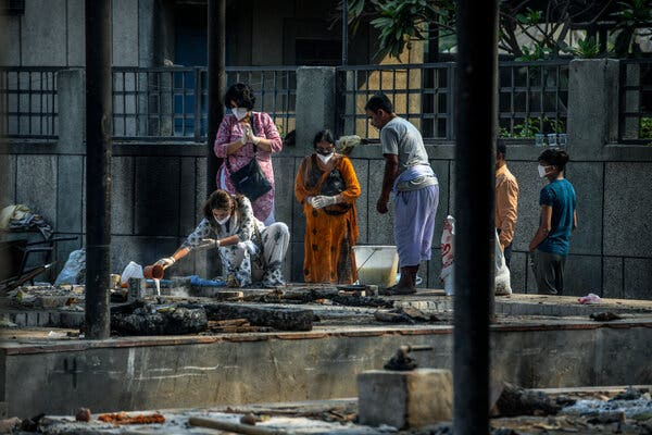 Families performing last rites at the Seemapuri cremation ground in Delhi. Crematories have been burning day and night because of Covid deaths.