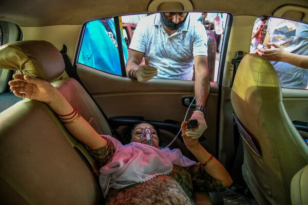 A Covid-19 patient receives oxygen in a parked car while waiting for a hospital bed to become available in New Delhi, as a volunteer checks her oxygen saturation level.