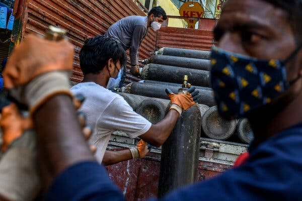 Workers unload tanks of oxygen at a shop in Delhi.Oxygen has become a precious resource in India as it fights a virulent wave of the coronavirus.