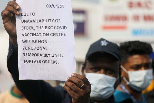 A worker informs people about a shortage of Covid-19 vaccines in Mumbai, India, this month. At the current vaccination rate, the country will not achieve herd immunity until the end of 2022.