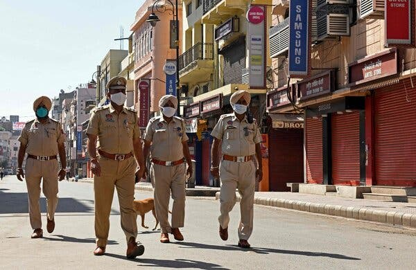 Police patrol a deserted market area during the lockdown imposed by the state government in Amritsar, India, on Saturday.