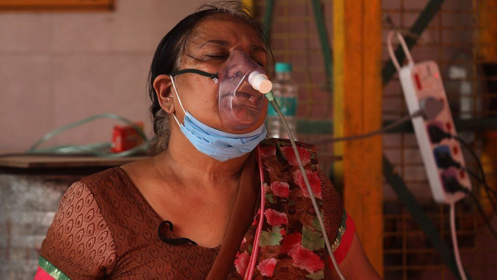 A woman in India breaths through an oxygen mask