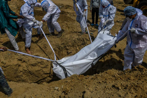 A body is lowered into a grave in New Delhi.