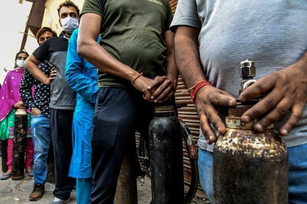 People wait in line to exchange empty oxygen tanks in Delhi last month.