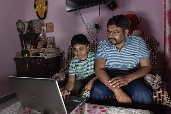 Mr. Kumar with his 10-year-old son, Akshay, in the Palam neighborhood in Delhi, India. Mr. Kumar lost his job as a civil engineer during last year's lockdown.