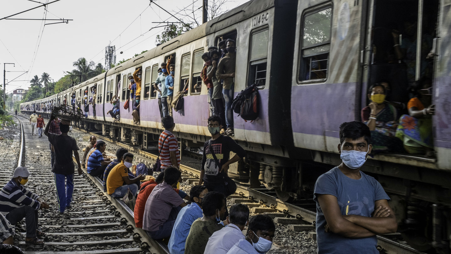 A train brimming with people wearing masks approaches Kolkata's Jadhavpur station in West Bengal, where campaigning was in full swing last week despite virus fears.