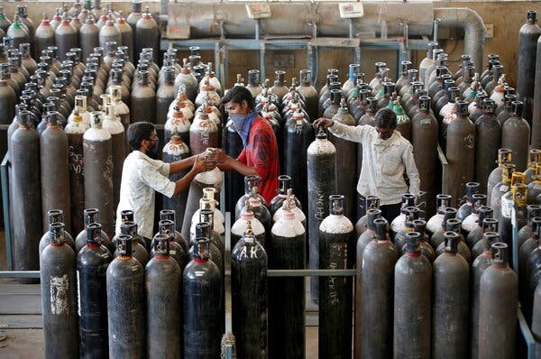 People carrying oxygen cylinders after refilling them in a factory in Ahmedabad, India, this weekend.