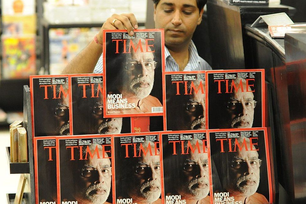 An Indian salesman arranges copies of Time magazine featuring a cover photo of Gujarat Chief Minister Narendra Modi at a store in Ahmedabad on March 18, 2012