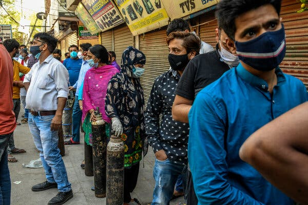 People wait in line with empty oxygen cylinders they will exchange for filled ones at a shop in south Delhi. About half of the world's global unmet need for medical oxygen is in India.