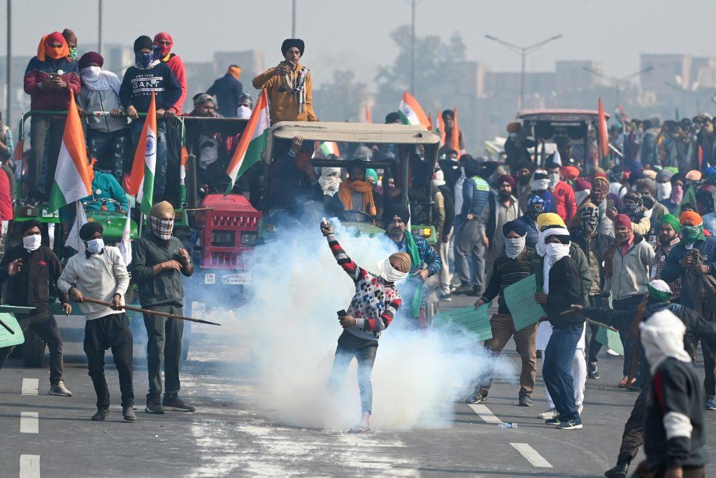 Un fermier renvoie du gaz lacrymogène tiré par les policiers en Inde. - AFP